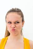 Junge Frau, die eine lustige Grimasse macht Lizenzfreie Stockfotos