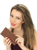 Junge Frau, die eine Milchschokolade-Stange hält Lizenzfreie Stockbilder