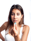 Junge Frau, die eine Pille hält lizenzfreies stockbild
