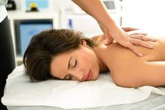 Junge Frau, die eine Rückenmassage in einer Badekurortmitte empfängt Lizenzfreie Stockfotos