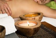Junge Frau, die eine Rückenmassage im Badekurortsalon empfängt Nahaufnahme einer Kerze und der Tücher Lizenzfreie Stockfotos