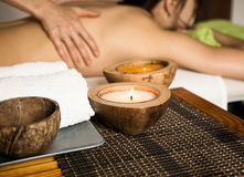 Junge Frau, die eine Rückenmassage im Badekurortsalon empfängt Nahaufnahme einer Kerze und der Tücher Stockfotografie