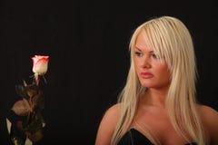 Junge Frau, die eine Rose anhält Lizenzfreie Stockbilder