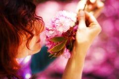 Junge Frau, die eine schöne Kirschblüte-Blüte, purpurrote Blumen riecht Frühlings-Magie Stockfotografie
