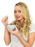 Junge Frau, die eine Schüssel Nüsse isst Stockfoto
