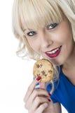 Junge Frau, die eine Schokolade Chip Cookie Biscuit isst Stockfoto