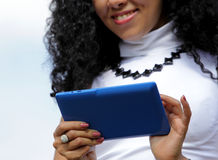 Junge Frau, die eine Tablette auf Himmelhintergrund verwendet Stockfotos