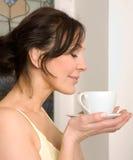 Junge Frau, die eine Tasse Tee genießt Stockbilder