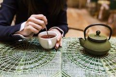 Junge Frau, die eine Tasse Tee pholding ist Stockfoto