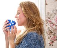 Junge Frau, die eine Tasse Tee trinkt stockfotografie