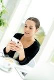 Junge Frau, die eine Textmeldung liest stockfotografie