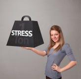 Junge Frau, die eine Tonne Druckgewicht anhält Stockbilder