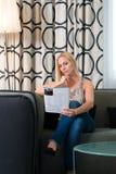 Junge Frau, die eine Zeitschrift im Hotelzimmer liest Stockfoto