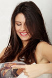 Junge Frau, die eine Zeitschrift liest Stockfotos