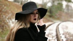 Junge Frau, die eine Zigarette raucht stock footage