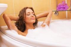 Junge Frau, die in einem Bad sich entspannt Lizenzfreie Stockfotografie
