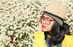Junge Frau, die in einem Blumengarten sitzt Stockbild