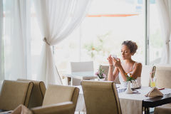 Junge Frau, die in einem Café unter Verwendung ihres Telefons sitzt Stockfotos
