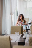 Junge Frau, die in einem Café unter Verwendung ihres Telefons sitzt Stockbild