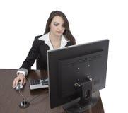 Junge Frau, die an einem Computer arbeitet Lizenzfreie Stockfotos