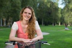 Junge Frau, die an einem Fahrrad sich lehnt Stockfoto
