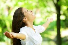 Junge Frau, die in einem Frühlings- oder Sommergarten sich freut Stockfoto