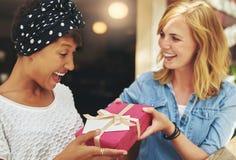 Junge Frau, die einem Freund ein Überraschungsgeschenk gibt Stockfotografie
