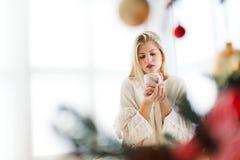 Junge Frau, die in einem hellen Raum, trinkender Kaffee sitzt Lizenzfreies Stockfoto