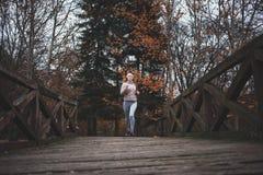 Junge Frau, die an einem kalten Tag im Park rüttelt Stockfotografie
