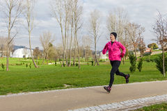 Junge Frau, die an einem kalten Wintertag läuft stockfoto