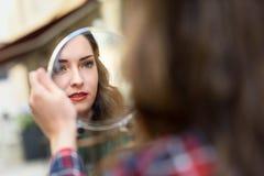 Junge Frau, die in einem kleinen Spiegel betrachtet Lizenzfreie Stockfotos
