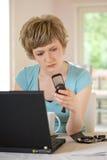 Junge Frau, die an einem Laptop arbeitet Stockfotos