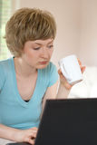 Junge Frau, die an einem Laptop arbeitet Lizenzfreies Stockfoto