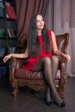Junge Frau, die in einem Lederstuhl sitzt Lizenzfreie Stockfotografie
