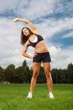 Junge Frau, die in einem Park ausarbeitet Lizenzfreies Stockfoto