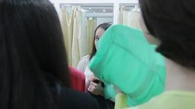 Junge Frau, die in einem Shop im Umkleideraum durch Verkäufer sich versteckt stock video footage