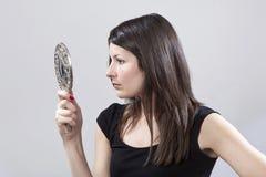 Junge Frau, die in einem Spiegel schaut Stockbilder