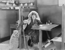 Junge Frau, die in einem Stand in einem Restaurant, versuchend, etwas aus einer Jutefasertasche heraus zu stehlen sitzt (alle dar Stockfotografie