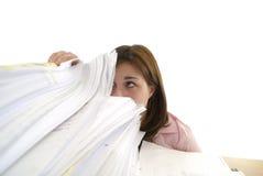 Junge Frau, die in einem Stapel Papieren schaut Stockfotos