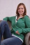 Junge Frau, die in einem Stuhl sitzt Lizenzfreie Stockbilder