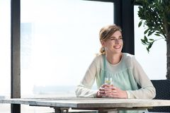 Junge Frau, die an einem Tisch mit einem Getränk an sitzt  Stockfoto