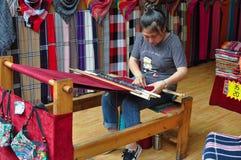 Junge Frau, die an einem Webstuhl arbeitet lizenzfreies stockfoto