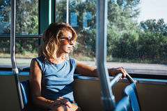 Junge Frau, die einen allgemeinen Bus reitet Stockfotos