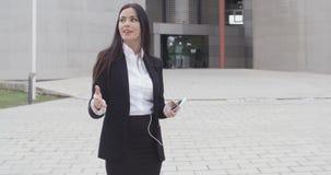 Junge Frau, die einen Anruf unter Verwendung der Ohrenpfropfen entgegennimmt stock footage