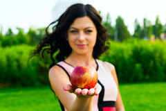 Junge Frau, die einen Apfel auf grünem Hintergrund hält Stockfotos