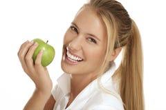 Junge Frau, die einen Apfel isst Stockfotografie