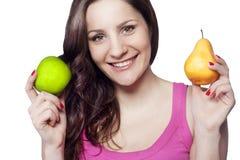 Junge Frau, die einen Apfel und eine Birne anhält Stockbild