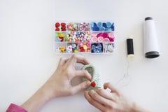 Junge Frau, die einen Babyschuh an ihrem strickenden Studio näht Lizenzfreie Stockfotos