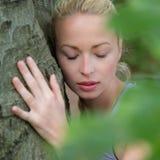 Junge Frau, die einen Baum umarmt lizenzfreie stockfotos