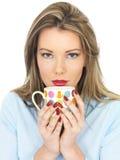 Junge Frau, die einen Becher Tee oder Kaffee trinkt Stockbild